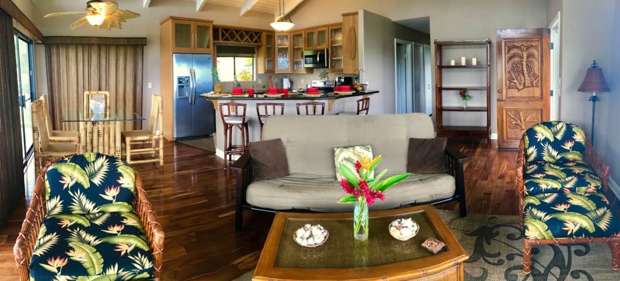 Main family area with wooden floors and sunset views at the Hale Makamaka.