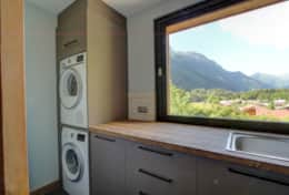 Utility room with a washing machine, a tumbler dryer ... and a window with views.