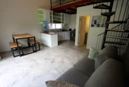 Loft Apartment #2. Downstairs area with a dining table and a couch to hang out on