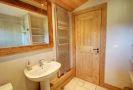 Upper floor bathroom with shower over the bath, wash basin, toilet and heated towel dryer