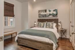 The 4th bedroom has a queen bed and peaceful gray and brown accents.